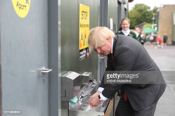Britain's Prime Minister Boris Johnson washes his hands at a sink in the playground during a visit to Bovingdon Primary School in Bovingdon Hemel...
