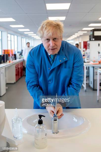 Britain's Prime Minister Boris Johnson washes his hands during a visit to the Mologic Laboratory in the Bedford technology Park north of London on...