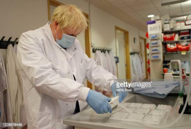 Britain's Prime Minister, Boris Johnson washes immunological assays during a visit to the Jenner Institute on September 18, 2020 in Oxford, England....