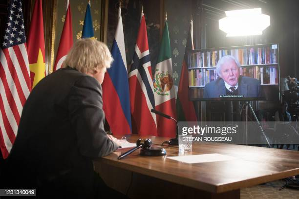Britain's Prime Minister Boris Johnson watches a video address by Sir David Attenborough as he chairs a virtual session of the UN Security Council on...