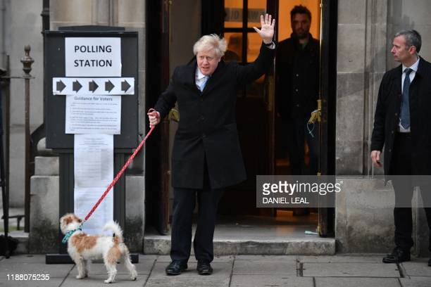 Britain's Prime Minister Boris Johnson waves as he arrives at a Polling Station to cast his ballot paper and vote, in central London on December 12...