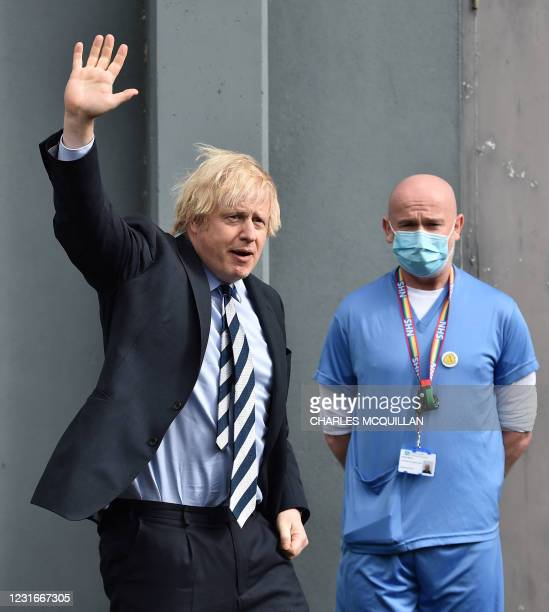 Britain's Prime Minister Boris Johnson waves as he leaves the Lakeland Forum Covid-19 vaccination centre on March 12, 2021 in Enniskillen, Northern...