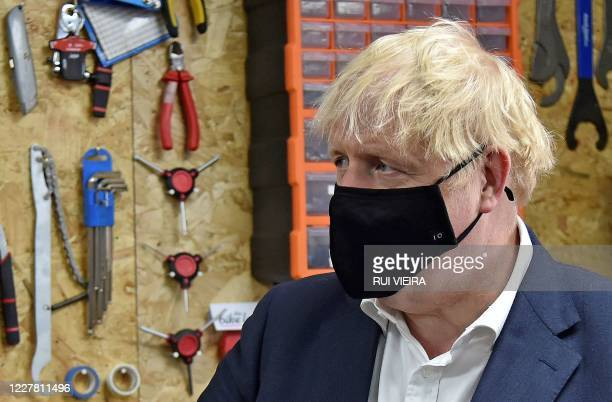 Britain's Prime Minister Boris Johnson wearing a black face mask featuring a number '10', due to the COVID-19 pandemic, talks to the owner of the the...