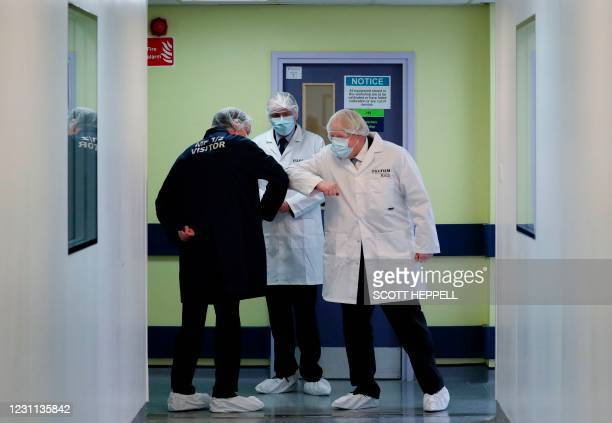 Britain's Prime Minister Boris Johnson , wearing a face covering and a FUJIFILM Diosynth Biotechnologies branded lab coat, elbow-bumps during his...