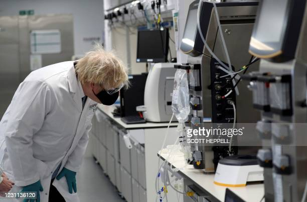 Britain's Prime Minister Boris Johnson, wearing a face covering and a FUJIFILM Diosynth Biotechnologies branded lab coat, reacts during his visit to...