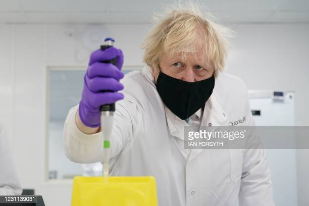 Britain's Prime Minister Boris Johnson wearing a face covering and lab coat uses a piece of lab equipment as he visits the QuantuMDx Biotechnology...