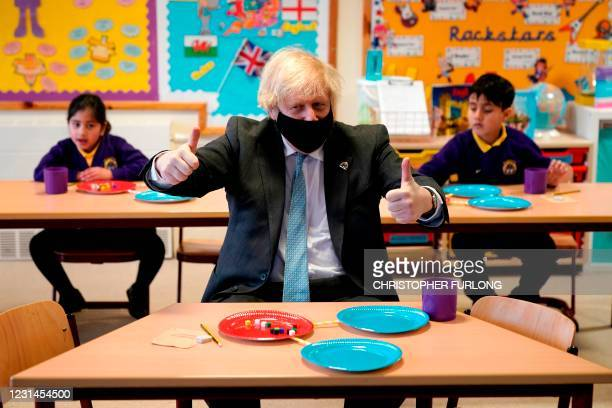 Britain's Prime Minister Boris Johnson, wearing a face covering and making the 'thumbs-up' sign, joins joins Year 2 pupils in a maths lesson, during...