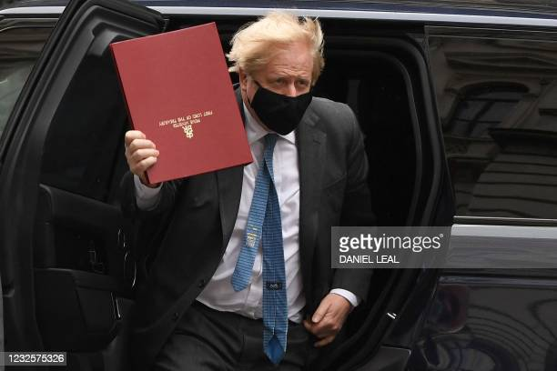 Britain's Prime Minister Boris Johnson wearing a face covering due to Covid-19, waves as he arrives back at 10 Downing Street in central London on...