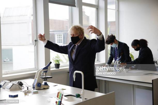 Britain's Prime Minister Boris Johnson, wearing a face covering due to Covid-19, gestures as he takes part in a science lesson at King Solomon...