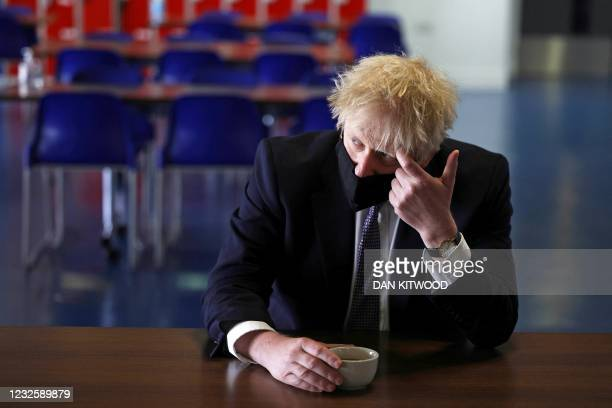 Britain's Prime Minister Boris Johnson, wearing a face covering due to Covid-19, speaks with pupils after taking part in a science lesson at King...
