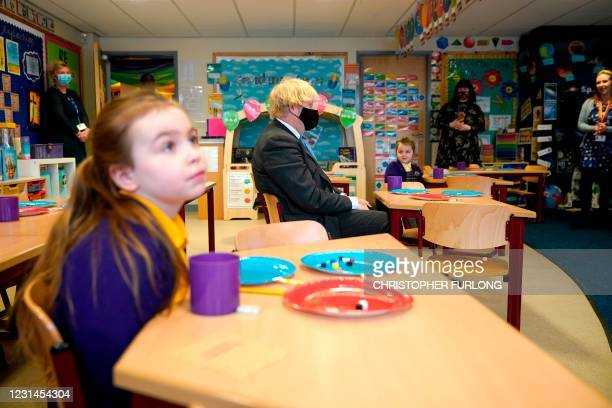 Britain's Prime Minister Boris Johnson, wearing a face covering, joins joins Year 2 pupils in a maths lesson, during his visit to St Mary's C.E....