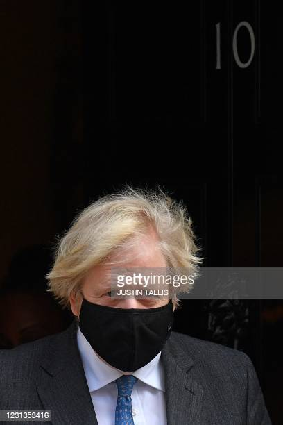 Britain's Prime Minister Boris Johnson, wearing a face covering, leaves 10 Downing Street in central London on February 24 to take part in the weekly...