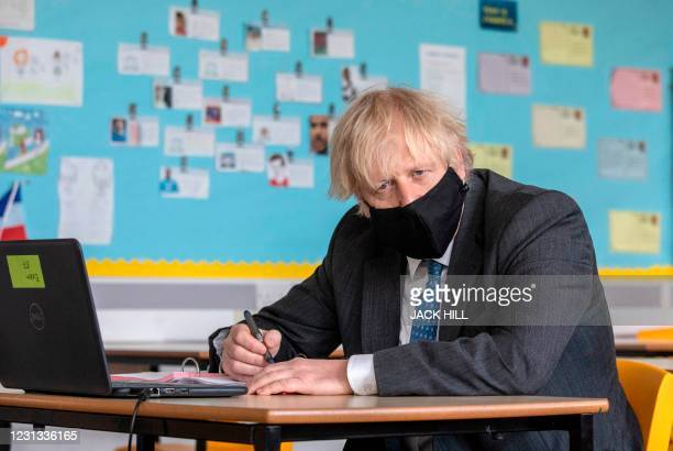 Britain's Prime Minister Boris Johnson, wearing a face covering, sits in front of a laptop computer as he takes part in an online lesson during his...