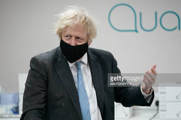 Britain's Prime Minister Boris Johnson wearing a face covering visits the QuantuMDx Biotechnology company in Newcastle upon Tyne, north east England,...