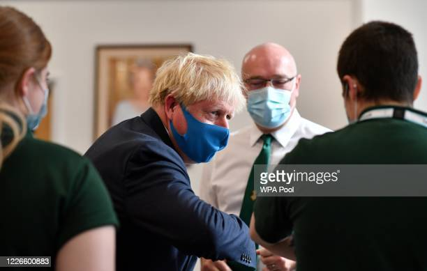 Britain's Prime Minister Boris Johnson , wearing a face mask or covering due to the COVID-19 pandemic, elbow bumps paramedics and science students as...