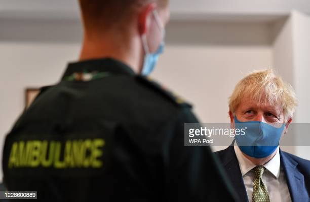 Britain's Prime Minister Boris Johnson wearing a face mask or covering due to the COVID19 pandemic talks with a paramedic as he visits the...