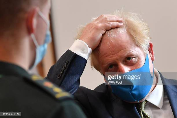 Britain's Prime Minister Boris Johnson , wearing a face mask or covering due to the COVID-19 pandemic, talks with a paramedic as he visits the...