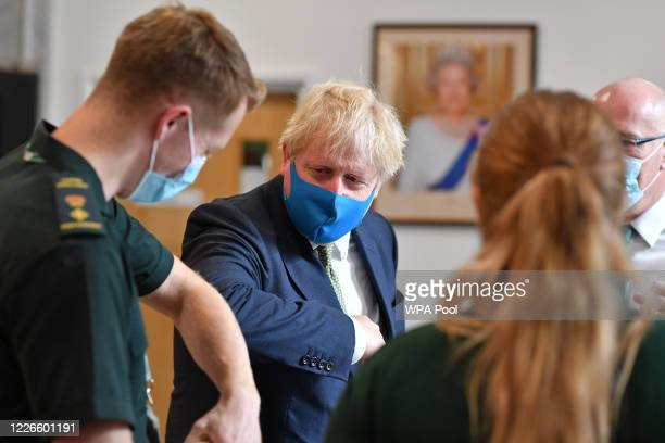 Britain's Prime Minister Boris Johnson , wearing a face mask or covering due to the COVID-19 pandemic, elbow bumps a paramedic as he visits the...