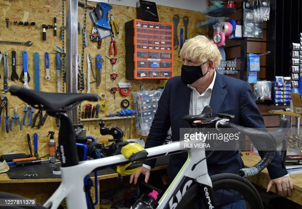 TOPSHOT Britain's Prime Minister Boris Johnson wearing a face mask or covering due to the COVID19 pandemic talks to the owner of the the Cycle Lounge...