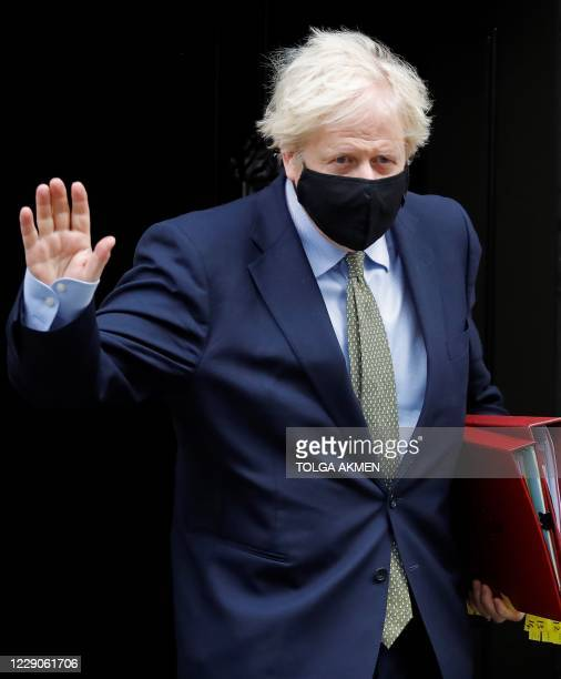 Britain's Prime Minister Boris Johnson wearing a face mask or covering due to the COVID-19 pandemic, waves as he leaves number 10 Downing Street in...