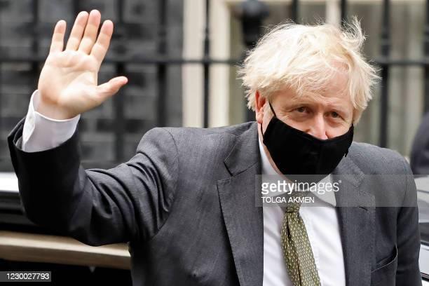 Britain's Prime Minister Boris Johnson, wearing a face mask or covering due to the COVID-19 pandemic, waves as he exits a car on return to 10 Downing...
