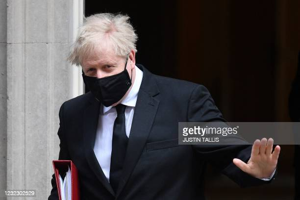 Britain's Prime Minister Boris Johnson, wearing a face mask to combat the spread of the novel coronavirus, waves as he leaves 10 Downing Street in...