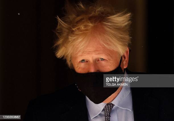 Britain's Prime Minister Boris Johnson, wearing a face mask to combat the spread of Covid-19, leaves 10 Downing Street in central London on June 10...