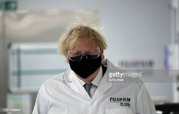 Britain's Prime Minister Boris Johnson, wearing a face mask to prevent the spread of the coronavirus, visits a pharmaceutical manufacturing facility...