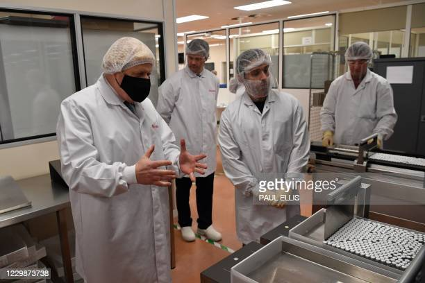 Britain's Prime Minister Boris Johnson , wearing a hair net and face covering reacts as he views the last minute quality testing of the 'fill and...