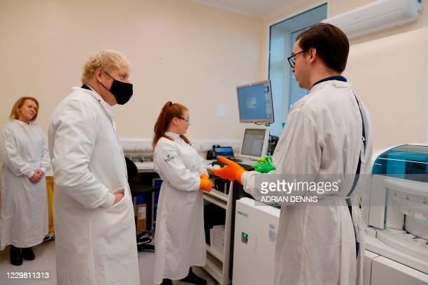 Britain's Prime Minister Boris Johnson wearing a mask because of the novel coronavirus pandemic Director PHE Porton Down Alex Sienkiewicz as...