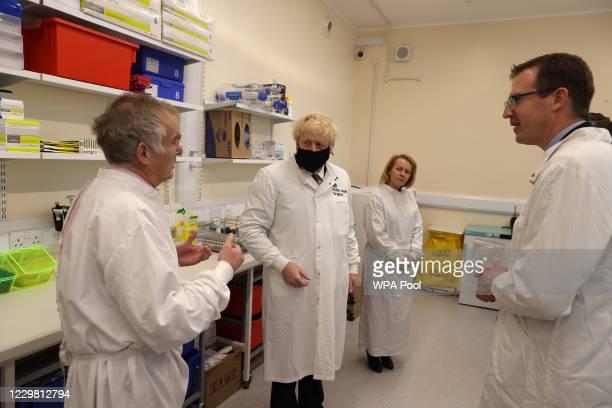 Britain's Prime Minister Boris Johnson wearing a mask because of the novel coronavirus pandemic talks to Dr Tim Brooks , Director PHE Porton Down...