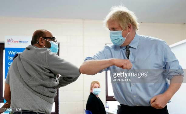 Britain's Prime Minister Boris Johnson wearing a protective face covering to combat the spread of the coronavirus, elbow bumps Ismail Patel after...