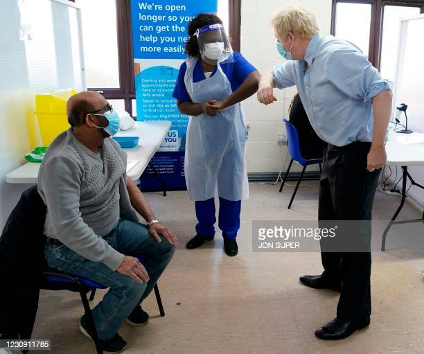 Britain's Prime Minister Boris Johnson wearing a protective face covering to combat the spread of the coronavirus, greets doctor Chantelle Ratcliffe...