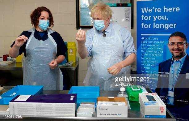 Britain's Prime Minister Boris Johnson wearing a protective face covering to combat the spread of the coronavirus, is shown how to prepare the...