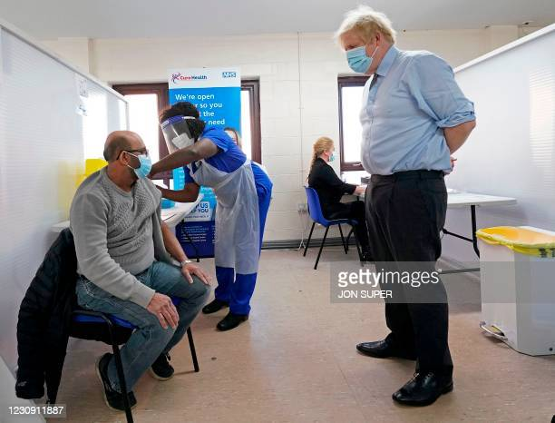 Britain's Prime Minister Boris Johnson wearing a protective face covering to combat the spread of the coronavirus, watches doctor Chantelle Ratcliffe...