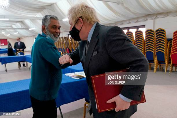 Britain's Prime Minister Boris Johnson wearing a protective face covering to combat the spread of the coronavirus, elbow bumps with the Community...
