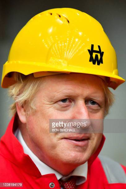 Britain's Prime Minister Boris Johnson wears a hard hat during his visit to Appledore Shipyard in south west England on August 25 as the historic...