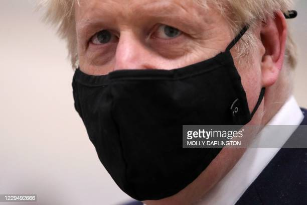Britain's Prime Minister Boris Johnson wears a protective face mask to prevent the spread of the coronavirus covid-19 during a visit to the East...