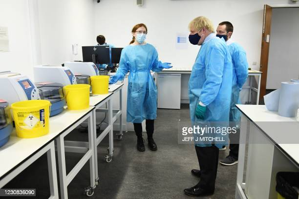 Britain's Prime Minister Boris Johnson wears PPE as he visits the Lighthouse Laboratory used for processing PCR samples at the Queen Elizabeth...