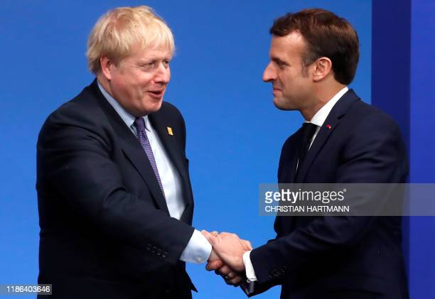 Britain's Prime Minister Boris Johnson welcomes France's President Emmanuel Macron upon his arrival for the NATO summit at the Grove hotel in...
