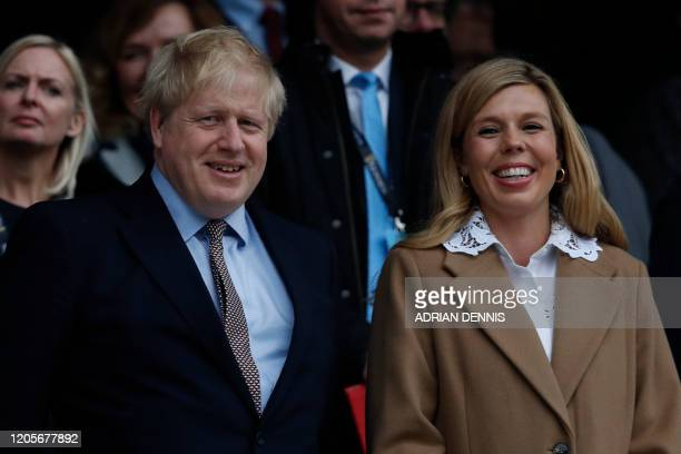 Britain's Prime Minister Boris Johnson with his partner Carrie Symonds attend the Six Nations international rugby union match between England and...