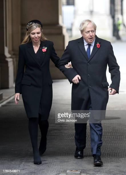 Britain's Prime Minister Boris Johnson with partner Carrie Symonds, on their way to meet veterans during the National Service of Remembrance at The...