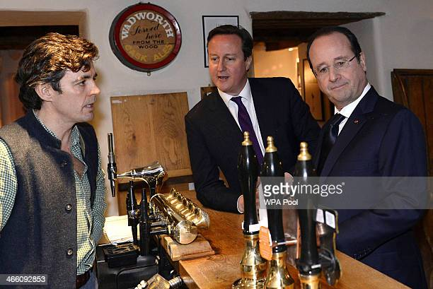 Britain's Prime Minister David Cameron and France's President Francois Hollande stand at the bar with landlord Archie OrrEwing as they arrive for an...