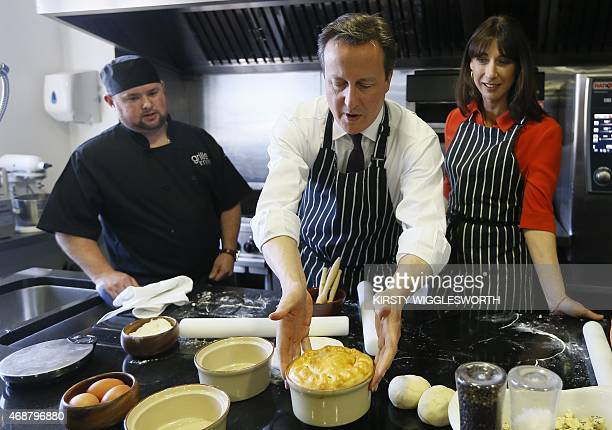 Britain's Prime Minister David Cameron and his wife Samantha make steak ale and stilton pies during a visit to Brains Brewery in Cardiff Wales on...