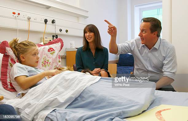 Britain's Prime Minister David Cameron and his wife Samantha talk to Scarlett Clarkson during a visit to the children's cancer ward at the John...