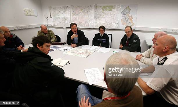 Britain's Prime Minister David Cameron attends a meeting of flood rescue services at police headquarters during a visit to flood hit areas on...