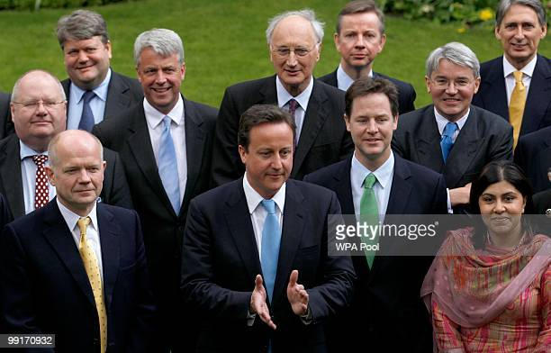 Britain's Prime Minister David Cameron calls an end to a group picture with his new cabinet ministers in the garden of Number 10 Downing Street on...