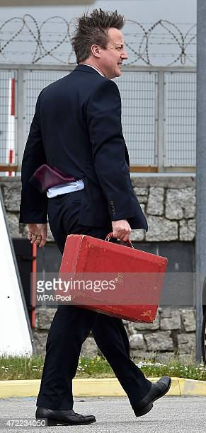 Britain's Prime Minister David Cameron disembarks from an aircraft at Newquay Airport to travel to an election rally in south west Britain on May 5...