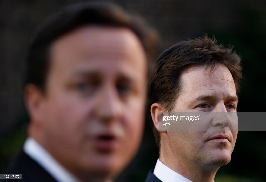 Britain's Prime Minister David Cameron (L) flanked by Deputy Prime Minister Nick Clegg (R) addresses guests at the Gay Pride reception in the garden at 10 Downing Street, in central London on June 16, 2010. Same-sex marriage is not legal in the United Kingdom. AFP PHOTO / POOL / Andrew WINNING