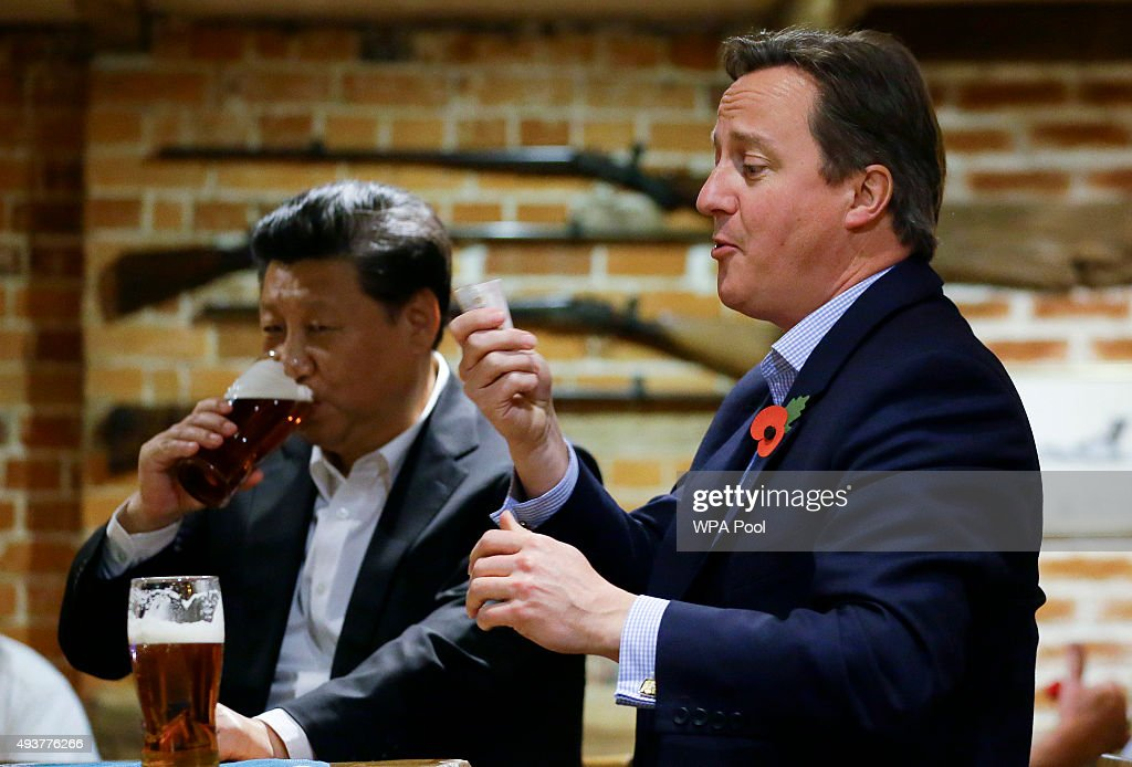 Britain's Prime Minister David Cameron gets out money to pay for drinks as China's President Xi Jinping drinks a pint of beer during a visit to the The Plough pub on October 22, 2015 in Princes Risborough, England. The President of the People's Republic of China, Mr Xi Jinping and his wife, Madame Peng Liyuan, are paying a State Visit to the United Kingdom as guests of The Queen. They will stay at Buckingham Palace and undertake engagements in London and Manchester. The last state visit paid by a Chinese President to the UK was Hu Jintao in 2005.